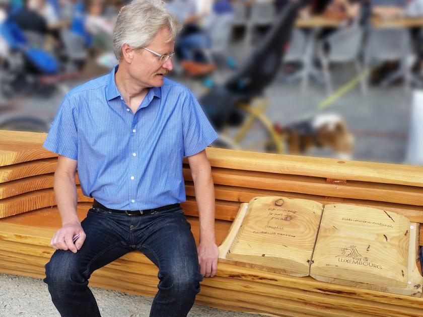 Reinhold liest im Holzbuch auf dem Place Guillaume II