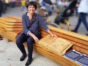 Ilona auf Holzbank mit Holzbuch auf dem Place Guillaume II